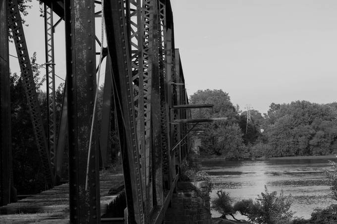 Photo of an old and partially burnt down railroad bridge. Published in DeSales University Arts Graph.