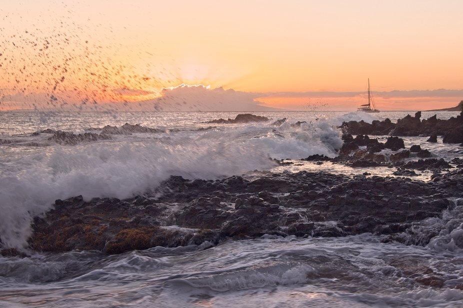 A small beautiful cove on the Maui coast near Kihei. A sailboat and sunset in the distance...