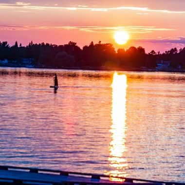 A lady in a red sundress enjoying a beautiful sunset paddleboard in Ranier, Mn. US