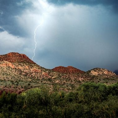 A monsoon rolls over the Verde Canyon hills with a single lightning strike