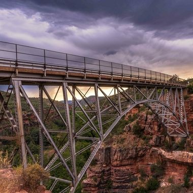 A summer monsoon brings a dark mood to this sunset picture of an iconic bridge on route 89A