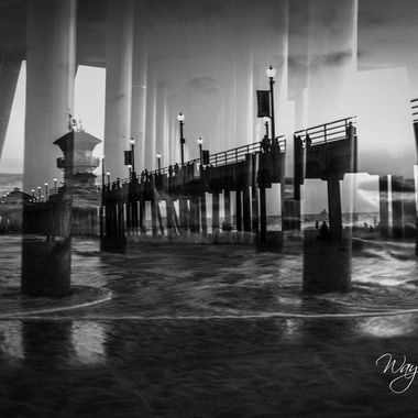 Black and white of double exposure Huntington Beach, CA Pier at sunset.