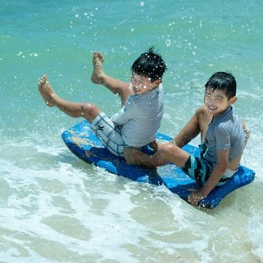 Cousins sharing a small wave on the North Shore of Oahu.