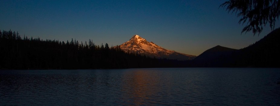A warm light hits the snow covered peak of Mount Hood