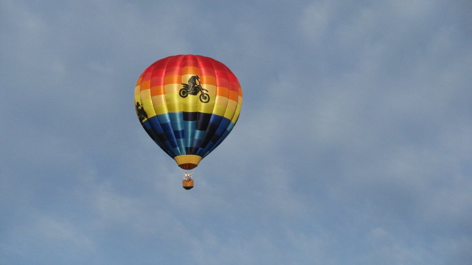 A colorful and fun hot air balloon drifting high across a blue and tranquil sky with motorcycle a...