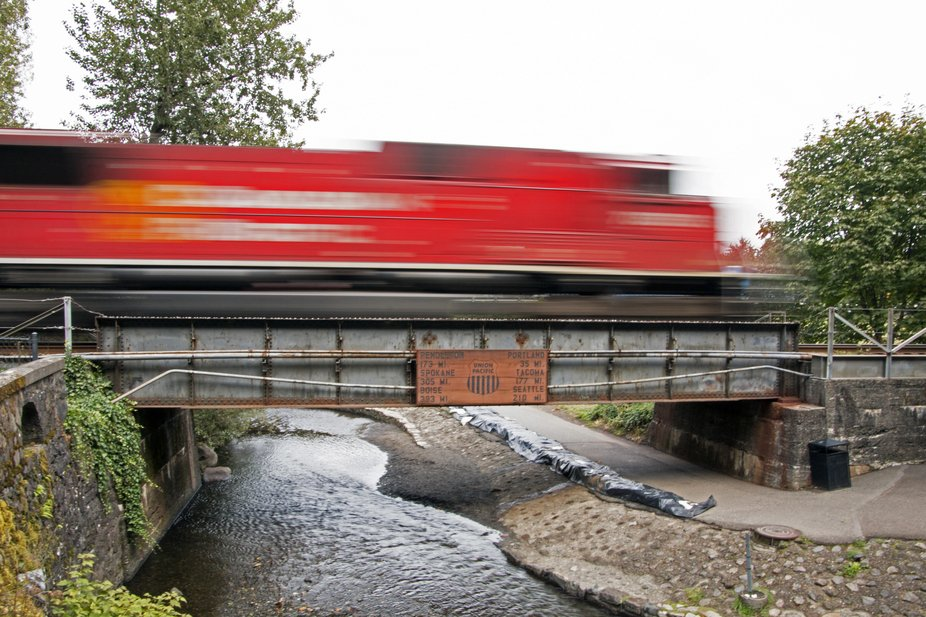Slow shutter on a train caboose crossing over a bridge while the rest of the scene is in focus