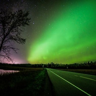 Catching the edge of the Northern Lights as the met the lights from the nearest town to make a beautiful contrast